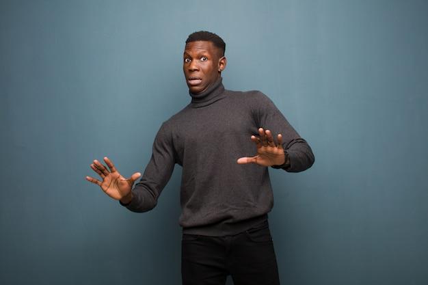 Jonge afro-amerikaanse zwarte man gevoel stom en bang, bang voor iets beangstigend, met handen open vooraan zeggen weg blijven over grunge muur