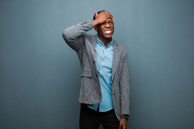 Jonge afro-amerikaanse zwarte man in paniek over een vergeten deadline, zich gestrest voelen, een puinhoop of een fout tegen de grunge muur moeten verdoezelen