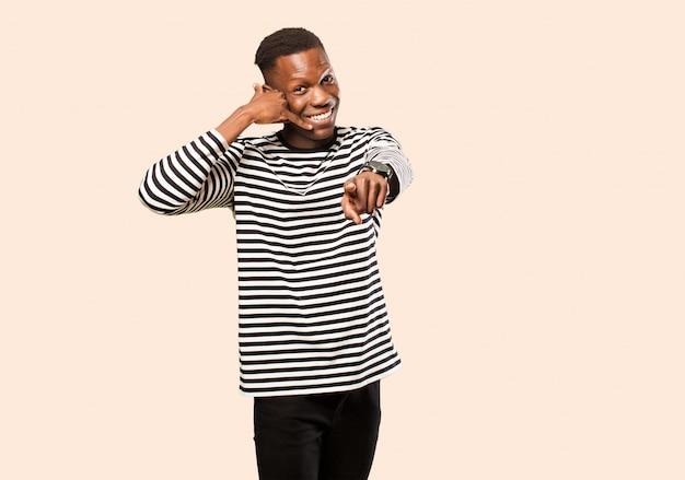 Jonge afro-amerikaanse zwarte man lacht vrolijk en wijst naar de camera tijdens het bellen van u later gebaar, praten over de telefoon op beige muur