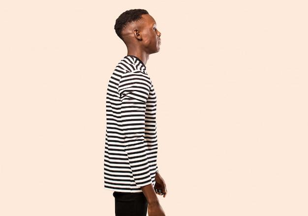 Jonge afro-amerikaanse zwarte man op profielweergave die ruimte vooruit wil kopiëren, denken, zich voorstellen of dagdromen tegen beige muur