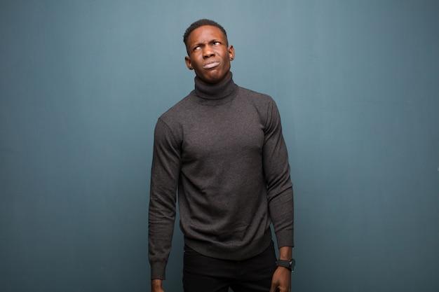 Jonge afro-amerikaanse zwarte man op zoek verbaasd en verward, benieuwd of probeert een probleem op te lossen of tegen grunge muur te denken
