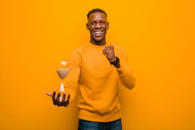 Jonge afro-amerikaanse zwarte man tegen oranje muur met een zandklok timer