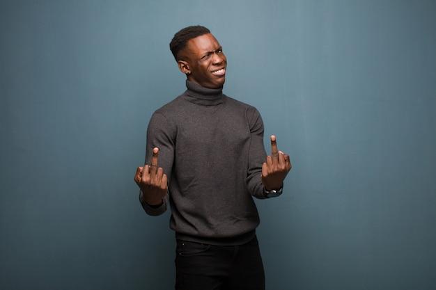 Jonge afro-amerikaanse zwarte man voelt provocerend, agressief en obsceen, flipping de middelvinger, met een opstandige houding over grunge muur