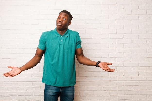 Jonge afro-amerikaanse zwarte man voelt zich verward en verward, onzeker over het juiste antwoord of de juiste beslissing, probeert een keuze te maken op de muur