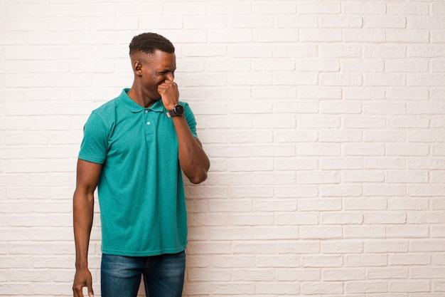 Jonge afro-amerikaanse zwarte man walgt gevoel, neus houden om te voorkomen dat een vieze en onaangename stank ruiken tegen bakstenen muur
