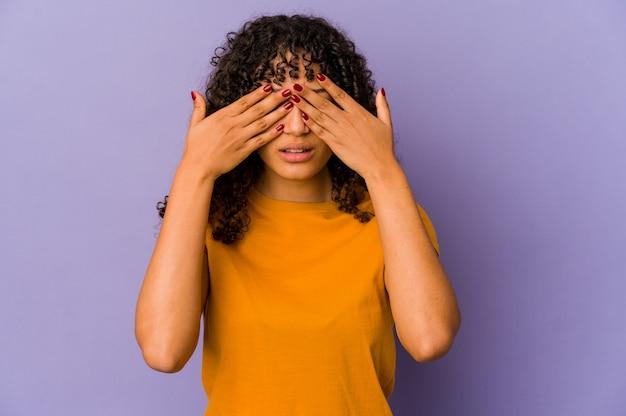 Jonge afro geïsoleerde vrouw bang voor ogen met handen