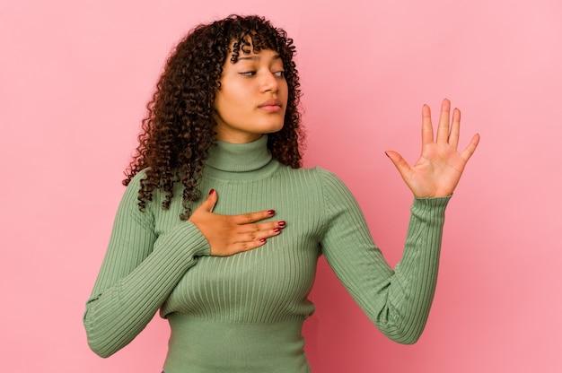 Jonge afro geïsoleerde vrouw die een eed aflegt, hand op borst legt