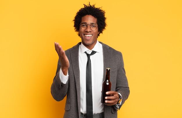 Jonge afro man die zich blij, verrast en opgewekt voelt, lacht met een positieve houding, een oplossing of idee realiseert