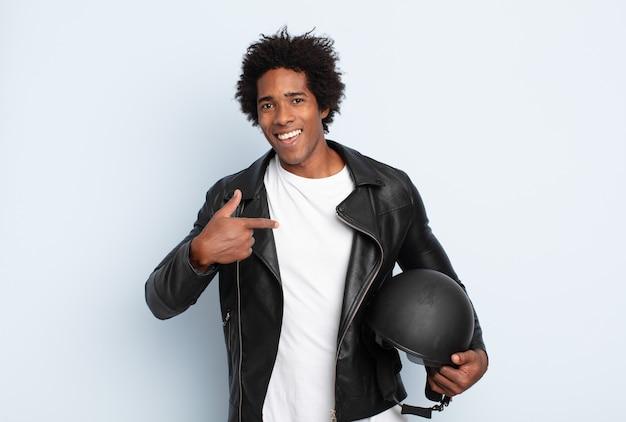 Jonge afro-man die zich blij, verrast en trots voelt en naar zichzelf wijst met een opgewonden, verbaasde blik
