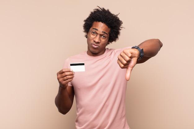 Jonge afro-man die zich boos, boos, geïrriteerd, teleurgesteld of ontevreden voelt, duimen naar beneden laat zien met een serieuze blik