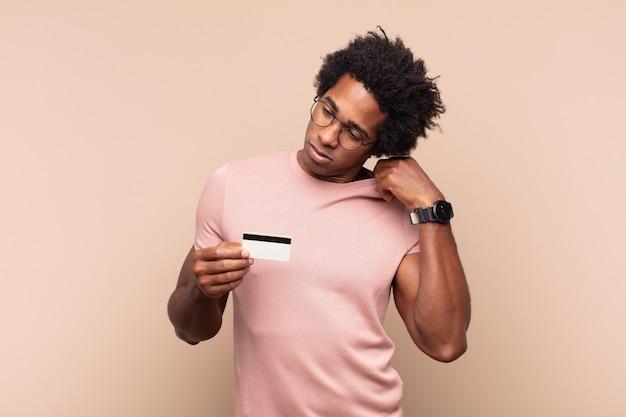 Jonge afro man die zich gestrest, angstig, moe en gefrustreerd voelt, de hals van het shirt trekt, gefrustreerd kijkt door het probleem