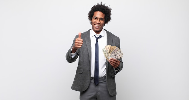 Jonge afro man die zich trots, zorgeloos, zelfverzekerd en gelukkig voelt, positief glimlacht met duimen omhoog