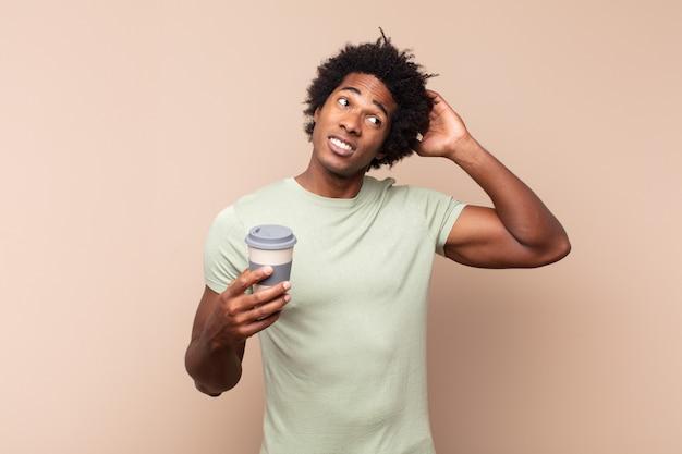 Jonge afro man die zich verbaasd en verward voelt, zijn hoofd krabt en naar de zijkant kijkt