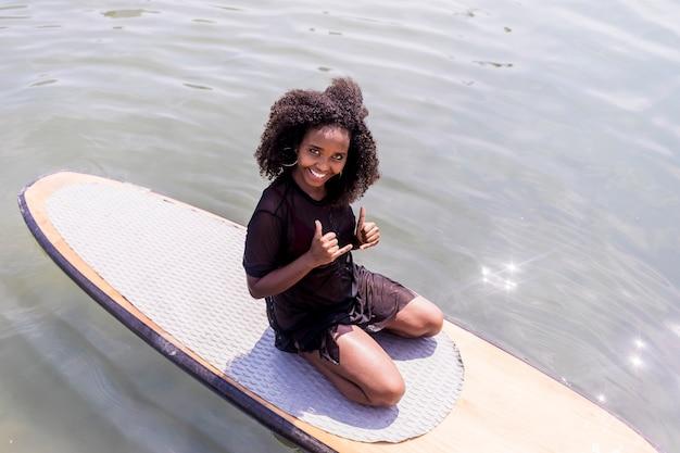 Jonge afro slank meisje zittend op paddle board in zee.