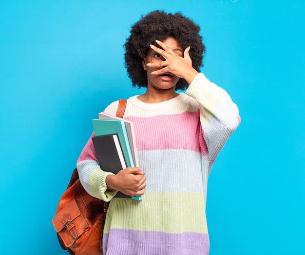 Jonge afro-studente die geschokt, bang of doodsbang kijkt, haar gezicht bedekt met de hand en tussen de vingers gluurt