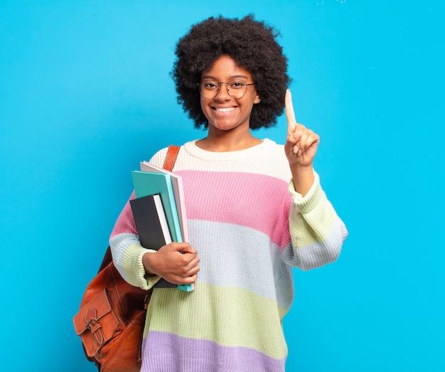 Jonge afro-studente die lacht en er vriendelijk uitziet, nummer één toont of eerst met de hand naar voren, aftelt
