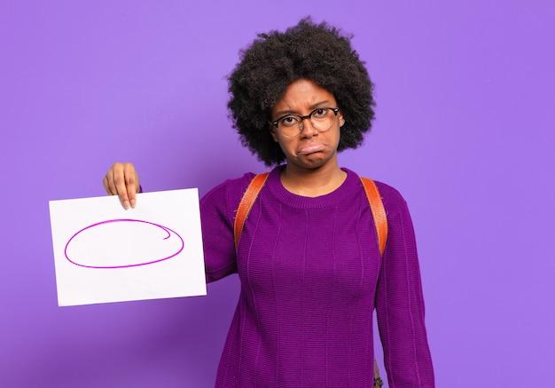 Jonge afro-studente die zich verdrietig en zeurderig voelt met een ongelukkige blik, huilend met een negatieve en gefrustreerde houding