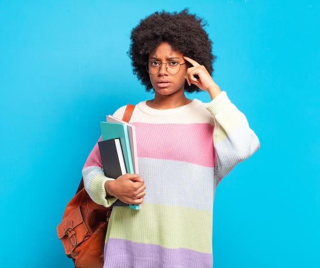Jonge afro-studente die zich verward en verbaasd voelt en laat zien dat je gek, gek of gek bent