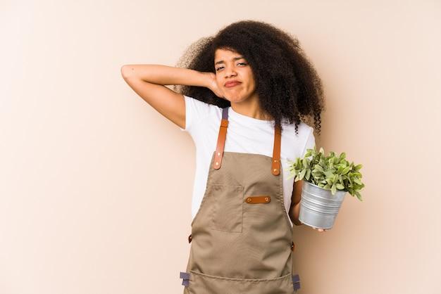Jonge afro tuinman die een plant houdt