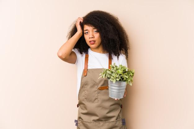 Jonge afro tuinman vrouw met een geïsoleerde plant geschokt, heeft ze belangrijke vergadering onthouden.