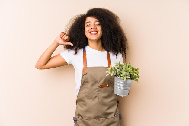 Jonge afro tuinman vrouw met een plant geïsoleerd voelt trots en zelfverzekerd, voorbeeld te volgen.