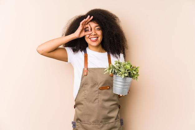 Jonge afro tuinman vrouw met een plant