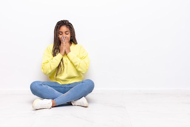Jonge afro-vrouw blij en opgewonden, verrast en verbaasd over de mond met handen, giechelend met een schattige uitdrukking