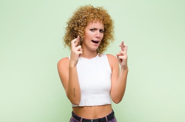 Jonge afro-vrouw die angstig vingers kruist en op geluk hoopt met een bezorgde blik tegen groene muur