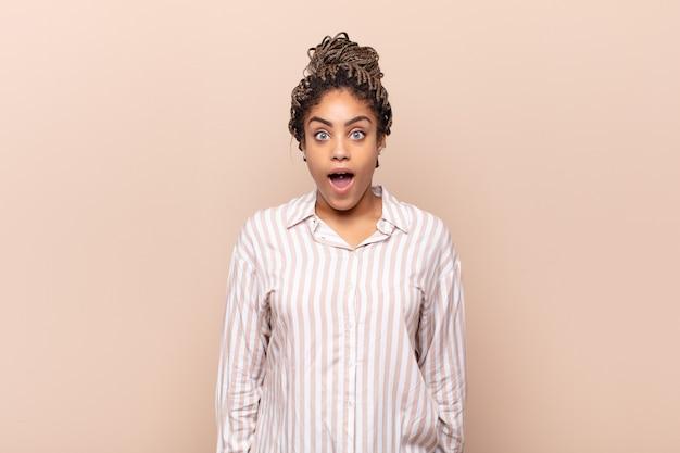 Jonge afro-vrouw die erg geschokt of verrast kijkt, starend met open mond en zegt wow