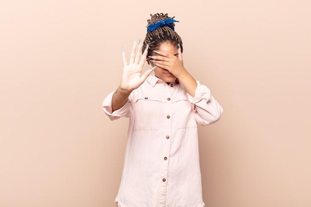 Jonge afro vrouw die gezicht bedekt met hand en andere hand naar voren zet om de camera te stoppen, foto's of afbeeldingen weigeren