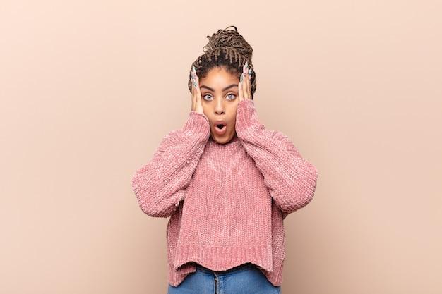 Jonge afro-vrouw die goofy en grappig kijkt met een dwaze schele uitdrukking, een grapje maakt en voor de gek houdt