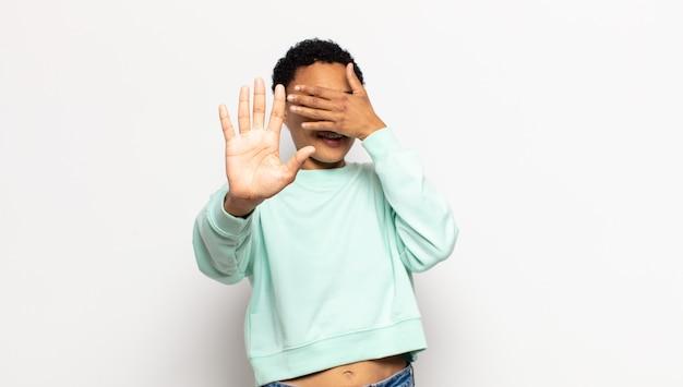 Jonge afro-vrouw die het gezicht bedekt met de hand en de andere hand naar voren steekt om de camera te stoppen, foto's of afbeeldingen weigert