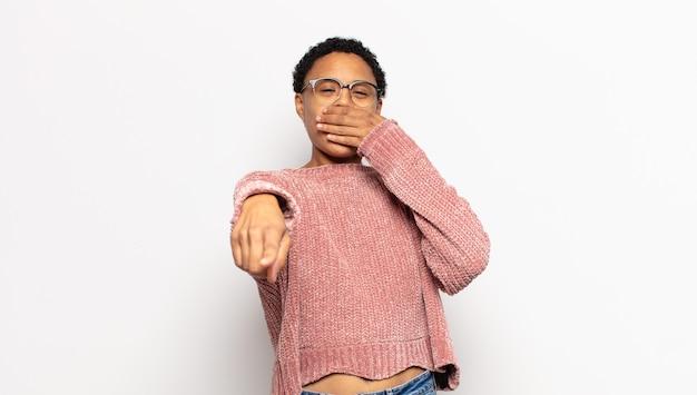 Jonge afro-vrouw die je uitlacht, naar de camera wijst en je belachelijk maakt of bespot