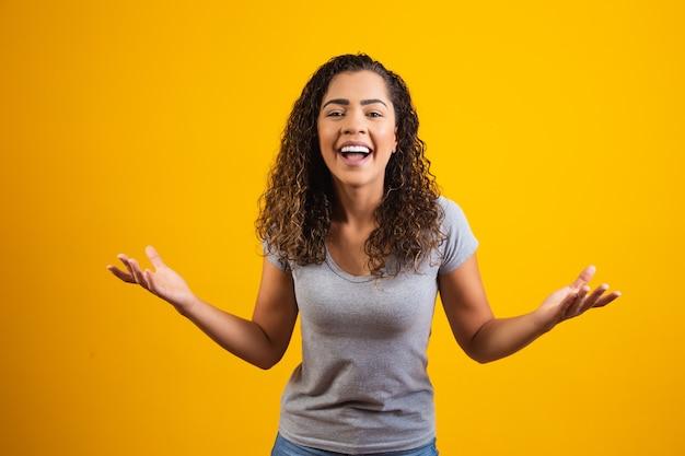 Jonge afro vrouw die lacht op gele achtergrond met vrije ruimte voor tekst. jonge student