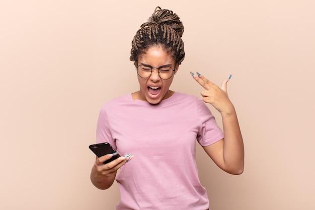 Jonge afro-vrouw die ongelukkig en gestrest kijkt, zelfmoordgebaar die pistoolteken met hand maakt, naar hoofd wijst. slimme telefoon concept