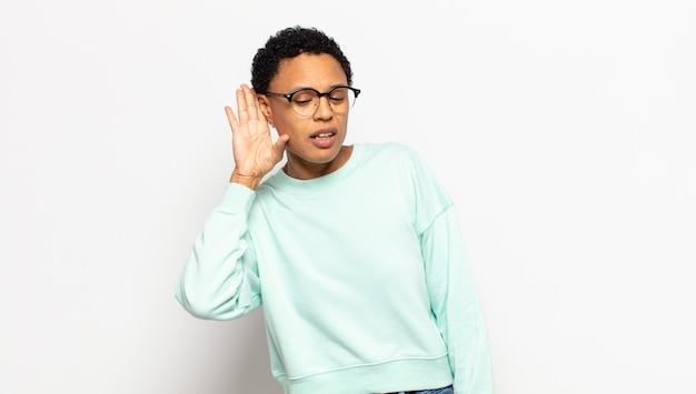 Jonge afro-vrouw die serieus en nieuwsgierig kijkt, luistert, probeert een geheim gesprek of roddel te horen, afluisteren
