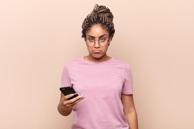 Jonge afro-vrouw die verdrietig en zeurderig is met een ongelukkige blik, huilend met een negatieve en gefrustreerde houding