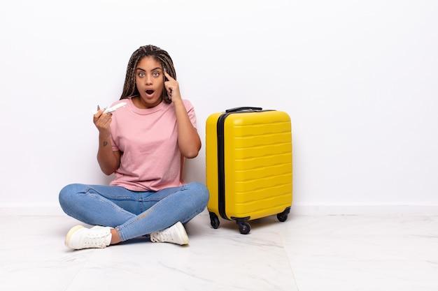 Jonge afro-vrouw die verrast, met open mond, geschokt kijkt en een nieuwe gedachte, idee of concept realiseert. vakantie concept