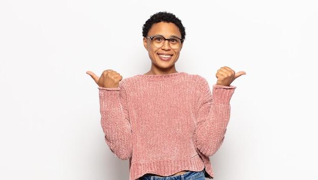 Jonge afro-vrouw die vreugdevol glimlacht en er gelukkig uitziet, zich zorgeloos en positief voelt met beide duimen omhoog