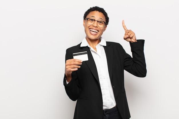 Jonge afro-vrouw die zich als een gelukkig en opgewonden genie voelt na het realiseren van een idee, opgewekt vinger opsteken, eureka!