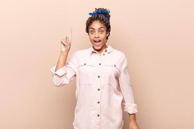 Jonge afro-vrouw die zich een gelukkig en opgewonden genie voelt na het realiseren van een idee, vrolijk vinger opstekend, eureka!