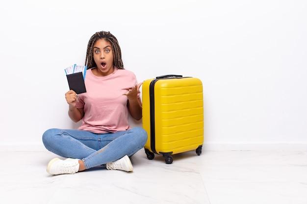 Jonge afro-vrouw die zich extreem geschokt en verrast, angstig en in paniek voelt, met een gestreste en geschokte blik. vakantie concept