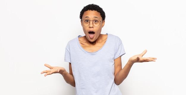 Jonge afro-vrouw die zich extreem geschokt en verrast, angstig en in paniek voelt, met een gestreste en geschokte blik