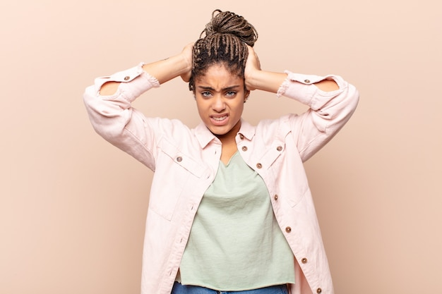 Jonge afro-vrouw die zich gefrustreerd en geïrriteerd voelt, ziek en moe is van mislukking, beu is met saaie, saaie taken