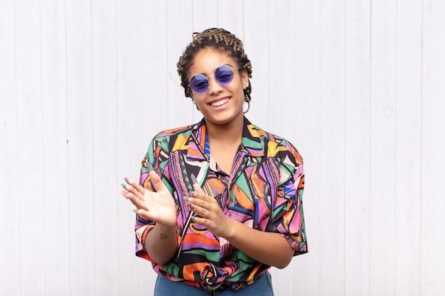 Jonge afro-vrouw die zich gelukkig en succesvol voelt, lacht en klapt in de handen, gefeliciteerd met een applaus
