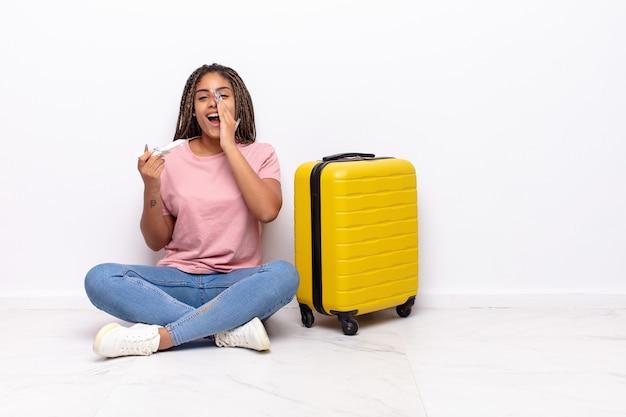 Jonge afro-vrouw die zich gelukkig, opgewonden en positief voelt, een grote schreeuw geeft met de handen naast de mond, roept. vakantie concept