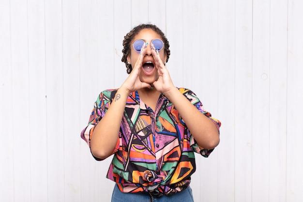 Jonge afro-vrouw die zich gelukkig, opgewonden en positief voelt, een grote schreeuw geeft met handen naast de mond, roept