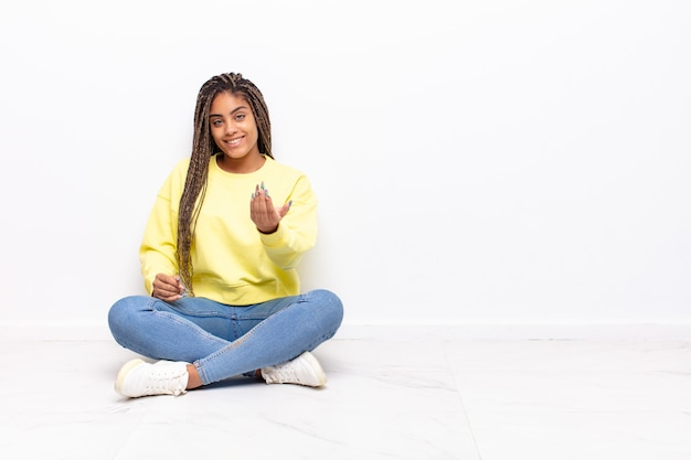Jonge afro-vrouw die zich gelukkig, succesvol en zelfverzekerd voelt, een uitdaging aangaat en zegt: kom maar op! of je verwelkomen