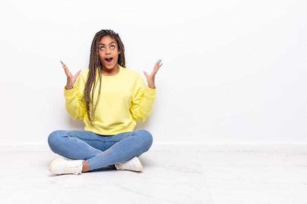 Jonge afro vrouw die zich gelukkig, verbaasd, gelukkig en verrast geïsoleerd voelt