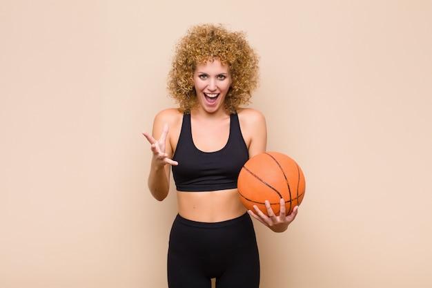 Jonge afro-vrouw die zich gelukkig, verbaasd, gelukkig en verrast voelt, zoals omg serieus te zeggen? ongelooflijk sportconcept